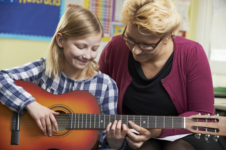 acoustic guitar: Teacher Helping Pupil To Play Guitar In Music Lesson