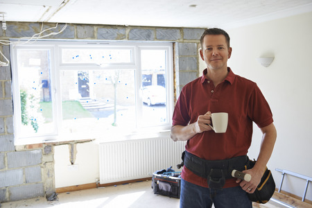 installing: Builder Carrying Out Home Improvements Taking A Break Stock Photo