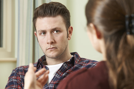 counsellor: Depressed Young Man Talking To Counsellor