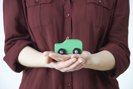 concept car: Woman Holding Model Car In Palm Of Hand Stock Photo
