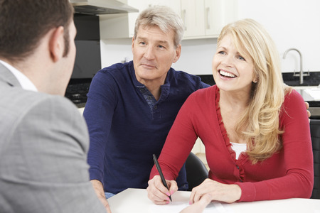 financial advisor: Mature Couple With Financial Advisor Signing Document At Home