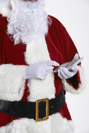 christmas debt: Close Up Of Santa Claus Holding Calculator Stock Photo