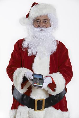 christmas debt: Studio Shot Of Santa Claus Holding Credit Card Reader Stock Photo
