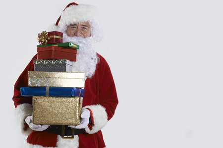 gift wrapped: Santa Claus Holding Pile Of Gift Wrapped Presents Stock Photo