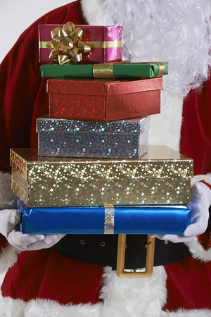 wrapped gift: Close Up Of Santa Claus Holding Pile Of Gift Wrapped Presents Stock Photo