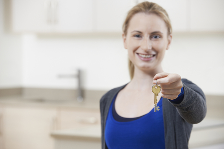 property ladder: Happy Young Woman Holding Keys To New Home Stock Photo