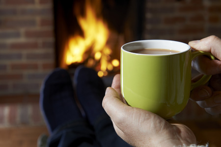 warm drink: Man With Hot Drink Relaxing By Fire