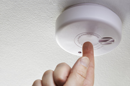 alarm button: Close Up Of Hand Testing Domestic Smoke Alarm