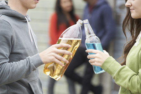 drinking alcohol: Close Up Of Teenage Group Drinking Alcohol Together Stock Photo