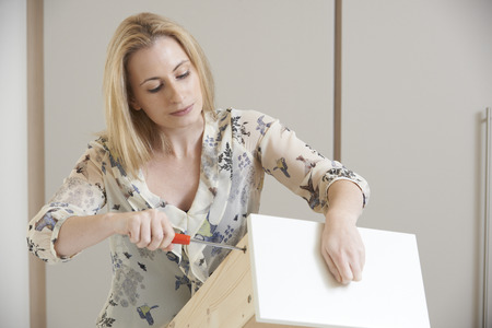 self assembly: Woman Putting Together Self Assembly Furniture Stock Photo