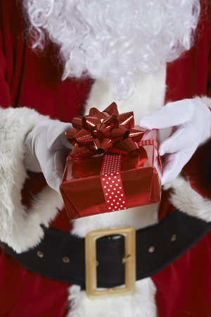 gift wrapped: Close Up Of Santa Claus Holding Gift Wrapped Present