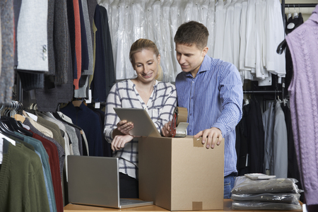 e store: Couple Running Online Clothing Store Packing Goods For Dispatch
