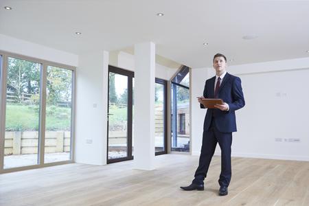 Estate Agent zich heen kijken Vacant Property Voor Valuation Stockfoto