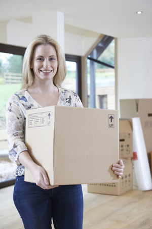 property ladder: Woman Moving Into New Home With Packing Box