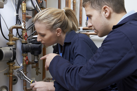 instructing: Female Trainee Plumber Working On Central Heating Boiler