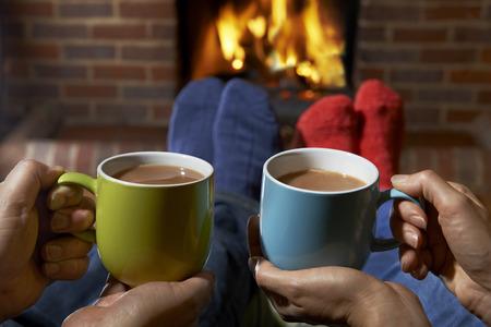 Paar mit heißem Getränk durch Feuer sich entspannt