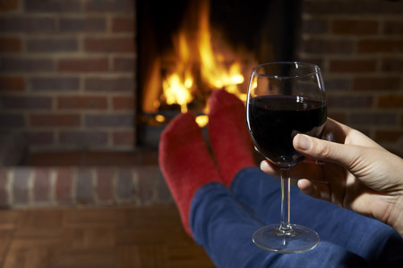 wine glasses: Woman With Glass Of Red Wine Relaxing By Fire