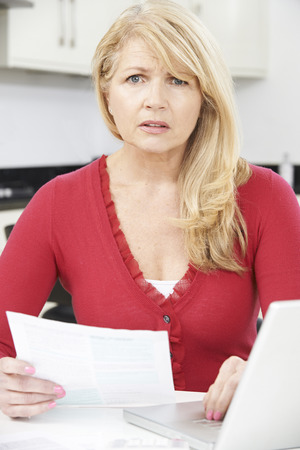 home finances: Worried Mature Woman Looking Reviewing Finances At Home