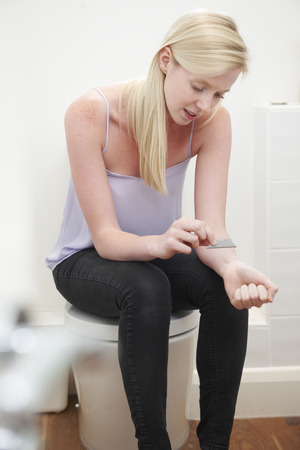 harming: Teenage Girl Self Harming In Bathroom With Knife Blade Stock Photo