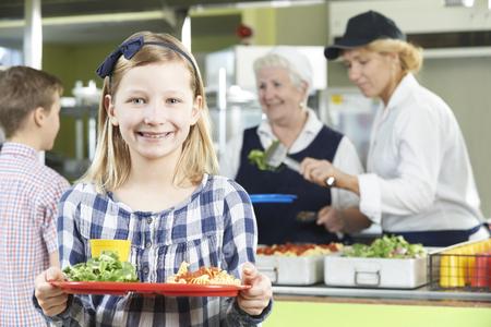 学校の食堂でヘルシーなランチと女子生徒 写真素材