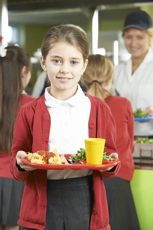 school girl uniform: Female Pupil With Healthy Lunch In School Cafateria Stock Photo