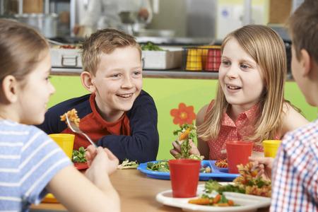Skupina žáků sedí u stolu v školní jídelna jíst oběd