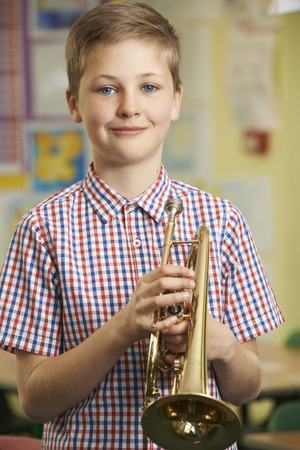 child boy: Boy Learning To Play Trumpet In School Music Lesson