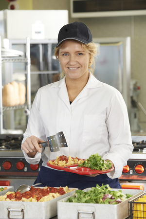 serving: Portrait Of Dinner Lady Serving Meal In School Cafeteria