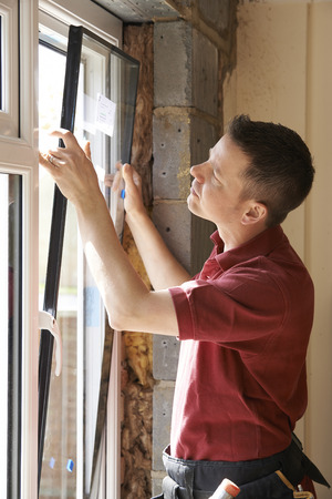 home interior: Construction Worker Installing New Windows In House Stock Photo
