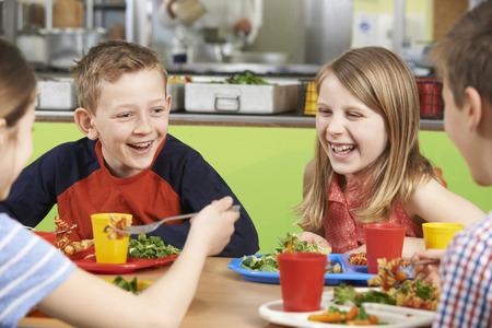 学校の食堂の食事を食べることでテーブルに座っている生徒のグループ