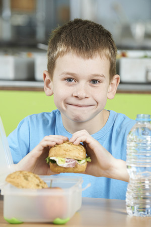 school cafeteria: Male Pupil Sitting At Table In School Cafeteria Eating Healthy Packed Lunch Stock Photo