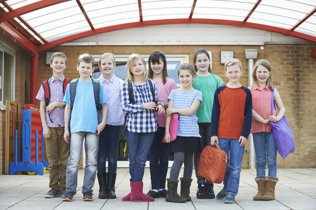 junior high: Portrait Of School Pupils Outside Classroom Carrying Bags