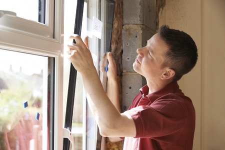 windows: Construction Worker Installing New Windows In House Stock Photo