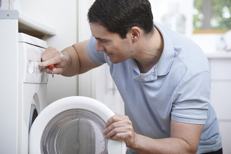 work clothes: Engineer Mending Domestic Washing Machine Stock Photo