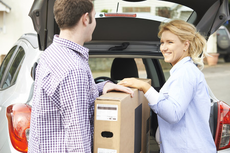 car trunk: Couple Unloading New Television From Car Trunk
