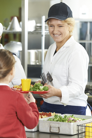 school cafeteria: Famale Pupil In School Cafeteria Being Served Lunch By Dinner Lady Stock Photo