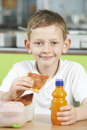 school cafeteria: Male Pupil Sitting At Table In School Cafeteria Eating Unhealthy Packed Lunch