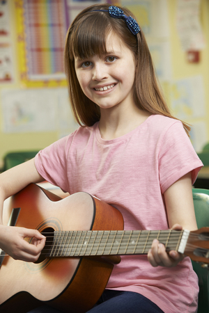 child smile: Girl Learning To Play Guitar In School Music Lesson