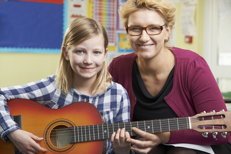 guitars: Teacher Helping Pupil To Play Guitar In Music Lesson