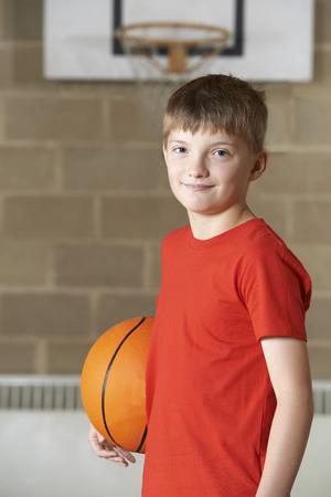 boys playing: Portrait Of Boy Holding Basketball In School Gym