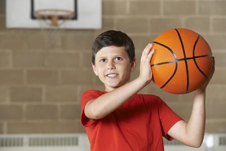school gym: Boy Shooting During Basketball Match In School Gym