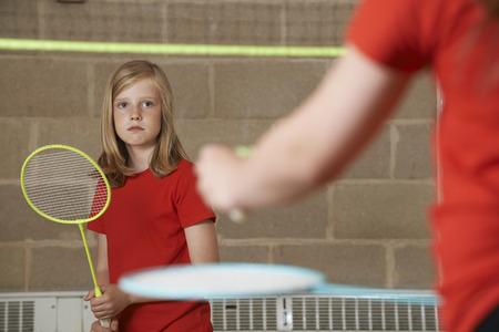 school gym: Two Girl Playing Badminton In School Gym