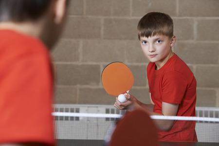 school gym: Two Boys Playing Table Tennis Match In School Gym