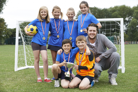 Victorious School Soccer Team With Medals And Trophy