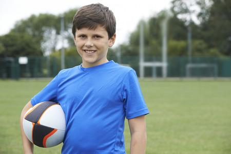 pelota rugby: Retrato de la explotaci�n agr�cola del muchacho Bola En la Escuela Campo de rugby Foto de archivo
