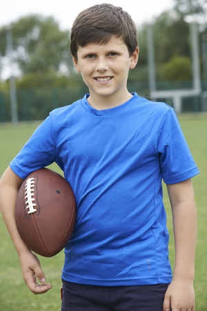 football pitch: Portrait Of Boy Holding Ball On School Football Pitch Stock Photo
