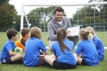 Coach Geven Team Talk To Elementary School Soccer Team