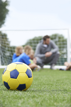 female soccer: Coach  And Team Discussing Soccer Tactics With Ball In Foreground Stock Photo