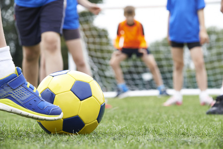 kicking ball: Close Up Of Childrens Feet In Soccer Match Stock Photo