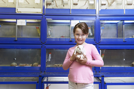pet store: Girl Holding Guinea Pig In Pet Store